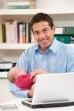 Vater mit dem neugeborenen Schätzchen, das vom Haus arbeitet Lizenzfreie Stockfotografie