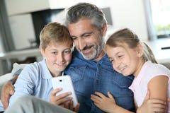 Vater mit den Kindern, die auf Smartphone spielen lizenzfreie stockfotografie