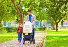 Vater mit den Kindern, die in Stadtpark gehen Lizenzfreie Stockfotos