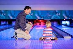Vater mit der kleinen Tochter, die Bowlingspiel spielt stockfotografie