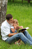 Vater mit der Schätzchentochter, welche die Bibel liest Stockfotos