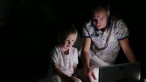 Vater mit Kinderaufpassendem Laptop in der Dunkelheit stock video