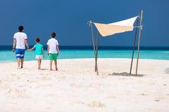 Vater mit Kindern am Strand Stockbild