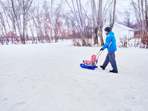 Vater mit Kinderweg im Winter der Schlitten auf Schnee Lizenzfreies Stockbild