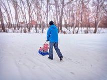 Vater mit Kinderweg im Winter der Schlitten auf Schnee Lizenzfreies Stockfoto