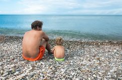 Vater mit kleinem Sohn sitzen in dem Meer Lizenzfreies Stockfoto