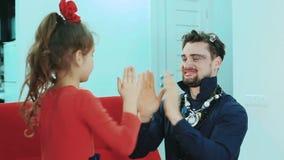 Vater mit Make-up und dem Tochterspielen Sie lachen das Lachen und das Scherzen stock video footage
