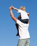 Vater mit seinem Sohn auf seinem zurück stockfotografie