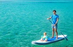 Vater mit seinem Sohn auf SUP Fastfood- Schaufeln Lizenzfreies Stockfoto
