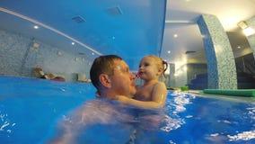 Vater mit seiner Tochter tauchen im Pool stock footage