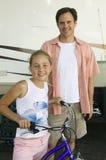 Vater mit Tochter auf Fahrrad nahe bei RV Stockbild