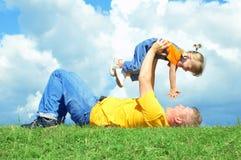 Vater mit Tochter auf grünem Gras Lizenzfreie Stockbilder