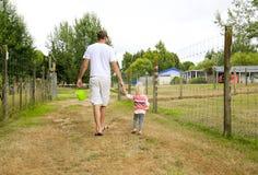 Vater mit Tochter, den Ackerlandbereich beobachtend Irgendwo in Neuseeland Lizenzfreie Stockfotografie