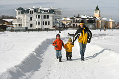 Vater mit zwei Jungen gehen auf Schneespur Lizenzfreie Stockfotografie
