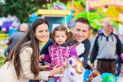 Vater, Mutter, Tochter, die Spaßmessefahrt, Vergnügungspark genießt lizenzfreies stockfoto