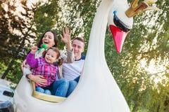 Vater, Mutter, Tochter, die Spaßmessefahrt, Vergnügungspark genießt Stockbild