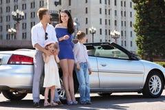 Vater, Mutter und Kinder stehen nahes Auto Stockbilder