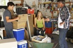 Vater-Organising Two Teenagers-Reinigungs-Garage für Garagenflohmarkt Stockfotografie