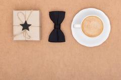 Vater ` s Tageshintergrund Tasse Kaffee, schöne anwesende und schwarze Fliege auf brauner Hintergrundebenenlage Dieses ist Datei  Stockfotos