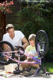 Vater-And Son Cleaning-Fahrrad zusammen stockbild