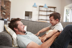 Vater And Son Cuddling auf Sofa Together stockfotografie