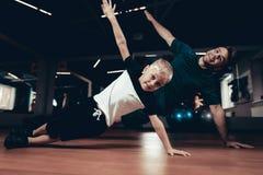 Vater-And Son Doing-Presse-Übungen in der Turnhalle lizenzfreie stockfotos