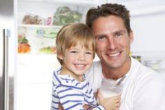Vater-And Son Getting-Snack vom Kühlschrank stockbilder