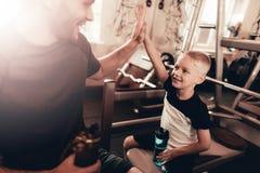 Vater And Son Have ein Bruch in der Turnhalle Hohe fünf lizenzfreies stockfoto