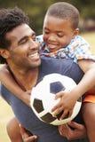 Vater-With Son Playing-Fußball im Park zusammen lizenzfreie stockfotografie