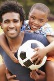Vater-With Son Playing-Fußball im Park zusammen lizenzfreie stockfotos