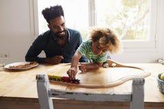 Vater And Son Playing mit Toy Train Set Lizenzfreies Stockbild