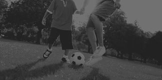 Vater-Son Playing Soccer-Park-Sommer-Konzept Lizenzfreie Stockbilder