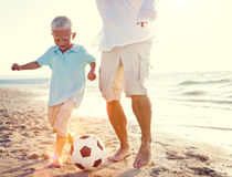 Vater-Son Playing Soccer-Strand-Sommer-Konzept stockbild