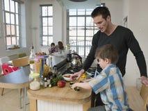 Vater-And Son Preparing-Salat während Familie, die im Hintergrund sitzt Lizenzfreies Stockfoto