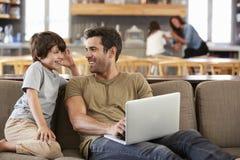 Vater And Son Sitting auf Aufenthaltsraum Sofa Using Laptop Together lizenzfreie stockfotografie