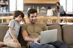 Vater And Son Sitting auf Aufenthaltsraum Sofa Using Laptop Together lizenzfreies stockbild