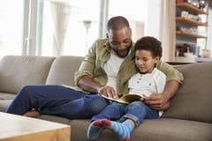 Vater And Son Sitting auf Sofa In Lounge Reading Book zusammen lizenzfreie stockbilder