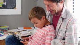Vater And Son Sitting im Schlafzimmer unter Verwendung Digital-Tablets stock video