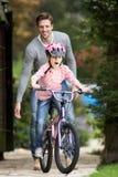 Vater-Teaching Daughter To-Fahrfahrrad im Garten Lizenzfreie Stockbilder