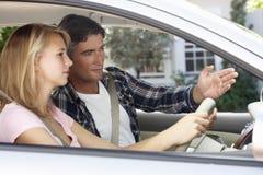 Vater Teaching Teenage Daughter zu fahren Lizenzfreie Stockfotografie