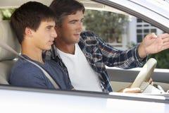 Vater Teaching Teenage Son zu fahren lizenzfreies stockfoto