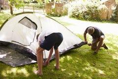 Vater And Teenage Son, das herauf Zelt auf Camping-Ausflug sich setzt lizenzfreie stockfotografie