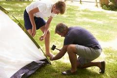 Vater And Teenage Son, das herauf Zelt auf Camping-Ausflug sich setzt stockfotos