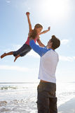 Vater-Throwing Daughter Into-Luft auf Strand Stockfotos