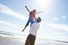 Vater-Throwing Daughter Into-Luft auf Strand Stockfoto