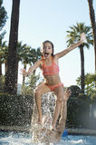Vater-Throwing Daughter In-Swimmingpool Stockfoto