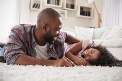 Vater Tickling Daughter As spielen sie Spiel im Aufenthaltsraum zusammen stockfotos
