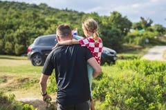 Vater trägt kleine Tochter in seinen Armen stockfotografie