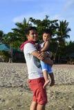 Vater- und Babysohn, der den Spaß aufwirft für Bild auf weißem Sandstrand hat stockbild