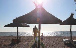 Vater und Junge, die auf dem Strand zur Sonnenuntergangzeit, Konzept der freundlichen Familie spielen lizenzfreie stockfotos